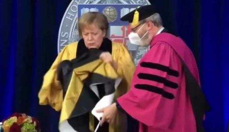 Как это носят? Меркель пыталась надеть почётную ленту выпускника — вышло смешно (ВИДЕО)